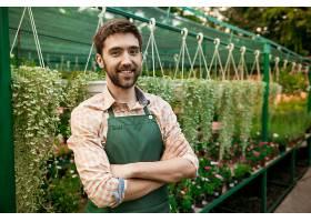 年轻英俊开朗的园丁微笑着在花丛中交叉双_776226501