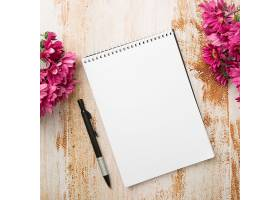 木质纹理背景上有钢笔和粉红色花朵的螺旋记_300423801