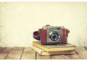 木质背景上的旧书上的老式相机古老的复古_111978001