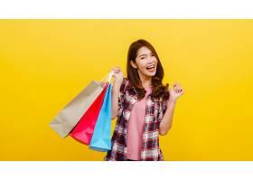 快乐兴奋的年轻亚洲女士手提购物袋穿着休_768585701