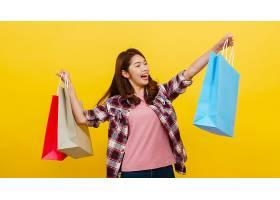 快乐兴奋的年轻亚洲女士手提购物袋穿着休_768585801