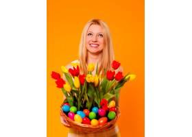 快乐女人提着装有春花和复活节彩蛋的篮子_1237574501