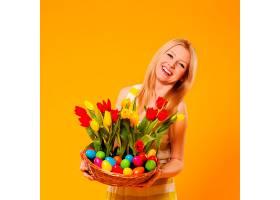 快乐女人提着装有春花和复活节彩蛋的篮子_1237576601