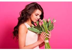 美丽娇艳的女人闻着春花的气息_1134217701