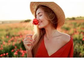 浪漫的金发女子手持鲜花走在令人惊叹的罂粟_991627401