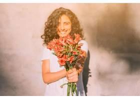 靠墙站着的年轻女子手里拿着星历红花_401883301