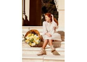 户外带着一束春花的美丽微笑的女人_1239683401