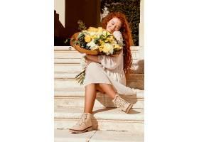 户外拿着一束春花的美丽快乐的女人_1239682901