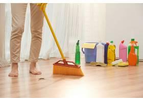 面目全非的女人用扫帚扫地的低位部分_569925201