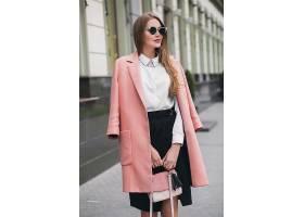 迷人时尚微笑的富婆穿着粉色外套走在城市街_1027210301