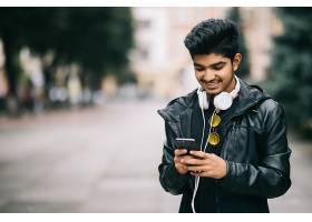 快乐的印度男人走路用智能手机听音乐戴_907731901