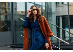 迷人时尚的女人走在城市商业街穿着暖和的_1157668801