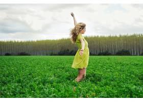 快乐的女孩双臂高举在草地上_89881601