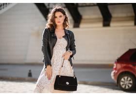 迷人的女人穿着时髦的服装走在街上提着钱_1154130201