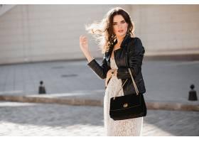 迷人的时尚女子穿着时髦的服装走在街上拿_1154136201