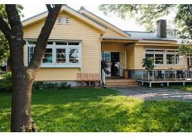迷人的黄色房子木窗和绿草如茵的花园_918532501
