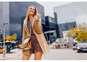快乐的金发女郎穿着春装在户外散步在现_991634101