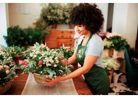 快乐的非洲妇女在桌子上摆放花篮_295507301