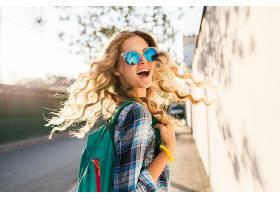 酷炫时髦的微笑快乐的金发女人背着背包走在_969946501