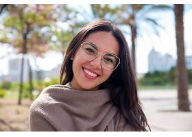 快乐美丽的年轻女子在城市公园的摄像机前摆_453017101