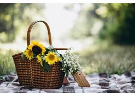 毛毯上有水果和鲜花的野餐篮子_305832401