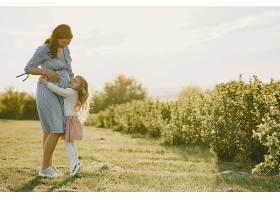 怀孕的母亲带着女儿在田里_965906101