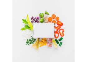 白色背景上的新鲜蔬菜上的空白螺旋记事本的_332929801