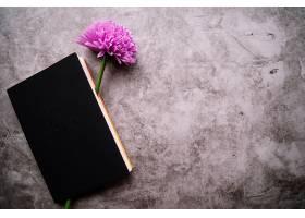 闭合的笔记本内有一朵假紫花背景为污点_332885001