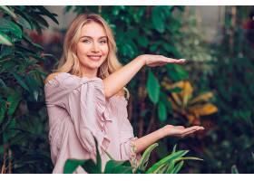 花园里一位微笑的年轻女子在手掌上炫耀着什_391146301