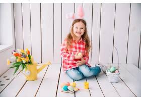 戴着兔子耳朵的小女孩坐在地板上手里拿着_383125301