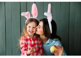 戴着兔子耳朵的母亲亲吻女儿的脸颊_383640401