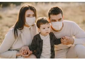戴着口罩的时尚家庭走在春天的田野上_835594401