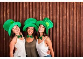 戴着圣帕特里克帽子的快乐年轻女子在墙上拥_401385301