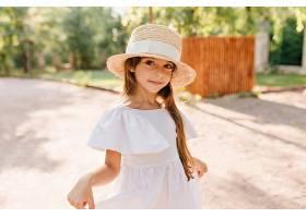 戴着大草帽的漂亮女孩一边在公园里用木栅栏_1048513001