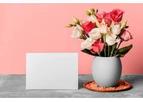 花瓶里的一束玫瑰花紧挨着一张空白的卡片_1206771501