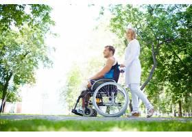 护送坐轮椅的年轻人_86536501