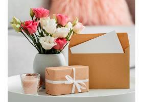 花瓶里的一束玫瑰花紧挨着包装好的礼物和_1206771601