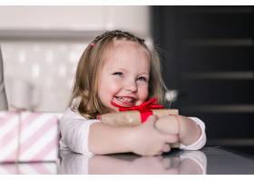 漂亮的小女孩把礼物放在腿上坐在厨房里_847146701