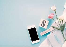 餐桌上有鲜花和智能手机的三月八日题词_385840201