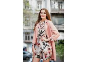 穿着粉色外套走在城市街道上的时髦迷人的微_1027154501