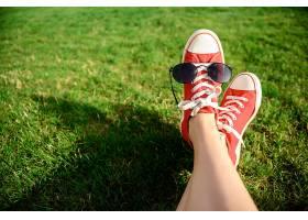 穿着红色鸡尾酒的腿躺在草地上的特写镜头_808468101
