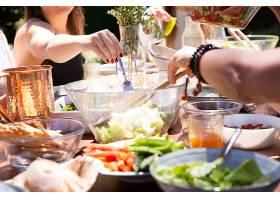 摆着食物的碗盘和拿着叉子的女性手的特写镜_499746801
