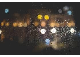 灯光模糊的透明玻璃窗上雨滴的特写_781067601