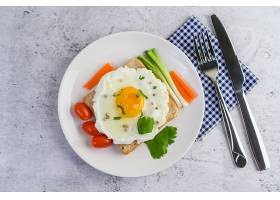 放在吐司上的煎蛋上面撒有胡萝卜和葱的胡_767651001