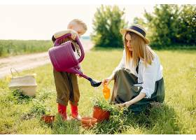 美丽的母亲带着小儿子在夏日的田野里_525289501