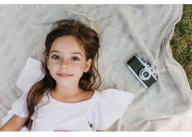 灵感四射的小女士棕色的大眼睛躺在花园里_1048515001