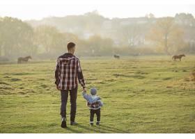 父亲带着年幼的儿子走在早晨的田野上_716969301