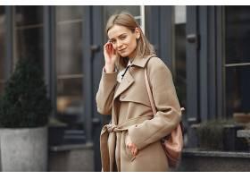 春城里一位穿着棕色大衣的优雅女子_771060301