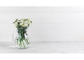 玻璃罐子里的菊花衬托着白色的木质背景_388250001