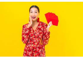 黄色墙上挂着红包的美丽亚洲年轻女子肖像_1204509001